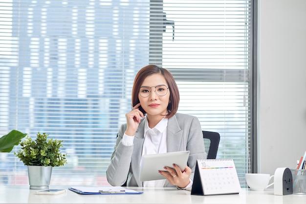 Portrait de la belle jeune femme d'affaires asiatique assis et à l'aide d'une tablette derrière la table en milieu de travail