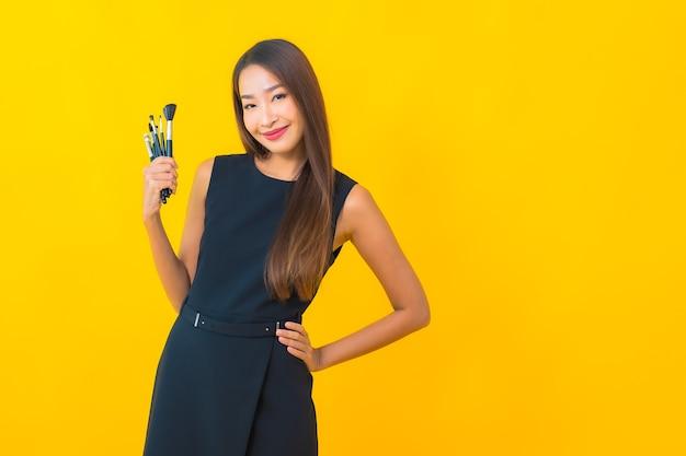 Portrait belle jeune femme d'affaires asiatique avec maquillage pinceau cosmétique sur fond jaune