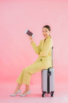 Portrait belle jeune femme d'affaires asiatique avec sac à bagages et passeport sur la couleur