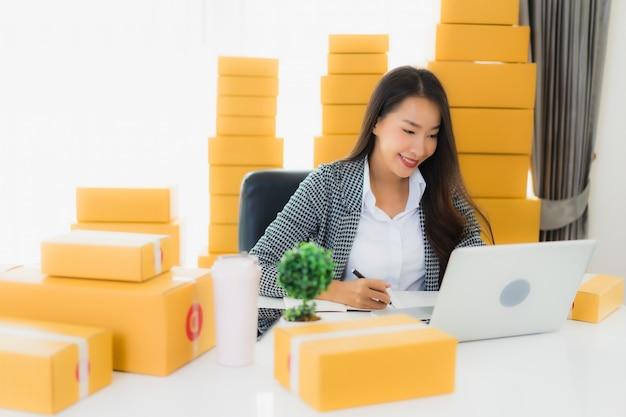 Portrait belle jeune femme d'affaires asiatique travail à domicile avec ordinateur portable téléphone portable avec boîte en carton prêt pour l'expédition