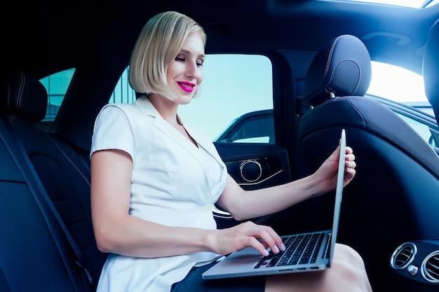 Portrait d'une belle jeune femme d'affaires blonde à coupe courte réussie avec du maquillage en robe de costume d'affaires blanche assise sur une chaise en cuir travaille avec des titres avec un ordinateur portable dans la voiture.