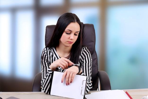 Portrait d'une belle jeune femme d'affaires faisant de la paperasse au bureau
