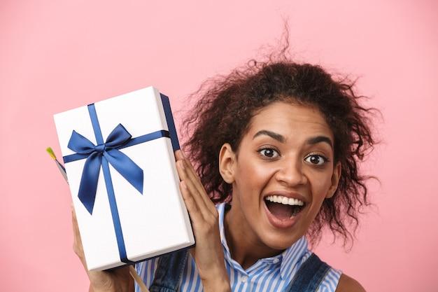 Portrait d'une belle jeune femme africaine heureuse excitée émotionnelle posant isolée sur un mur rose tenant une boîte cadeau.