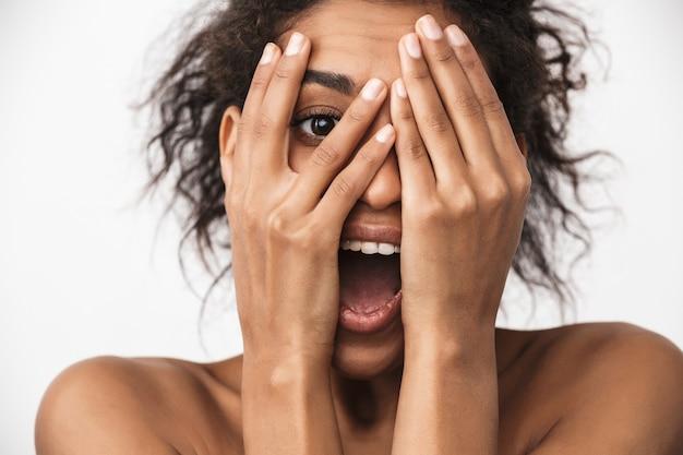Portrait d'une belle jeune femme africaine heureuse posant isolé sur un mur blanc couvrant le visage avec les mains.