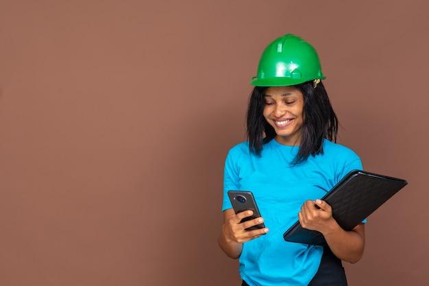Portrait d'une belle jeune femme africaine travaillant dans le bâtiment portant un chapeau entendu, utilisant son téléphone portable, portant un document, debout sur un fond uni