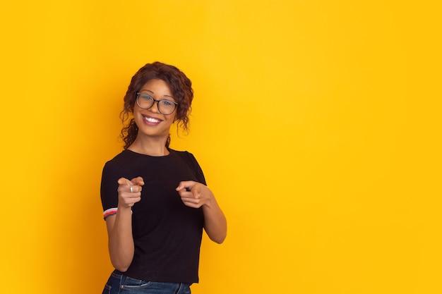 Portrait de la belle jeune femme afro-américaine sur jaune,