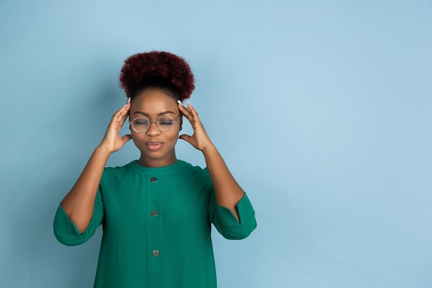Portrait d'une belle jeune femme afro-américaine sur un mur bleu émotionnel et expressif