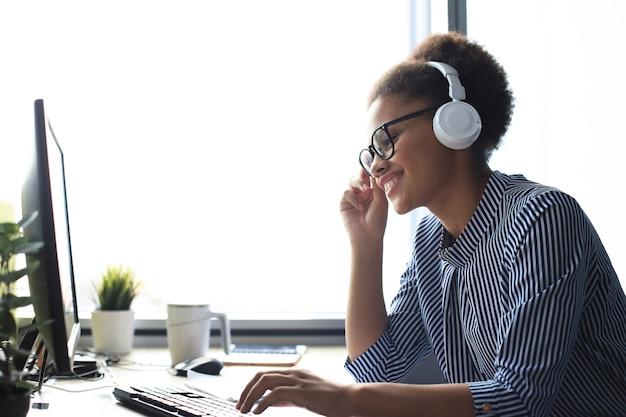 Portrait de la belle jeune femme afro-américaine travaillant sur ordinateur et bavardant assis dans des écouteurs.
