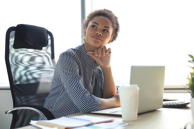Portrait de la belle jeune femme afro-américaine travaillant avec un ordinateur portable assis à la table.