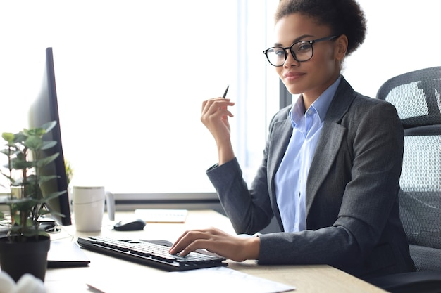 Portrait de la belle jeune femme afro-américaine travaillant sur ordinateur tout en étant assis à la table.