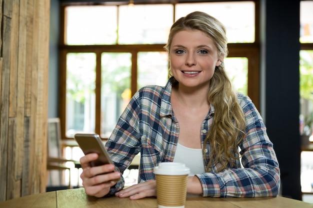 Portrait de la belle jeune femme à l'aide de téléphone portable au café