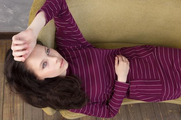 Portrait de la belle jeune femme allongée sur le canapé et penser.