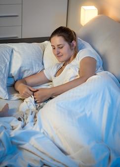 Portrait d'une belle jeune femme allongée dans son lit la nuit et utilisant une tablette numérique