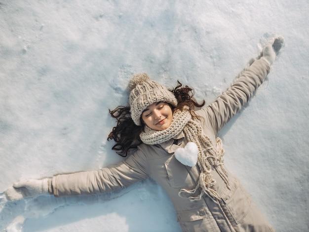 Portrait d'une belle jeune femme allongée sur un lac de neige gelé pendant des vacances d'hiver ensoleillées