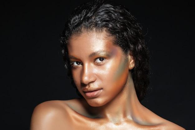 Portrait de la belle jeune femme américaine avec un maquillage brillant sur fond noir