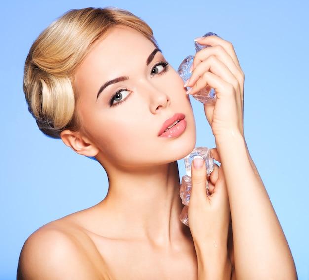 Portrait de la belle jeune femme applique la glace au visage sur le bleu.