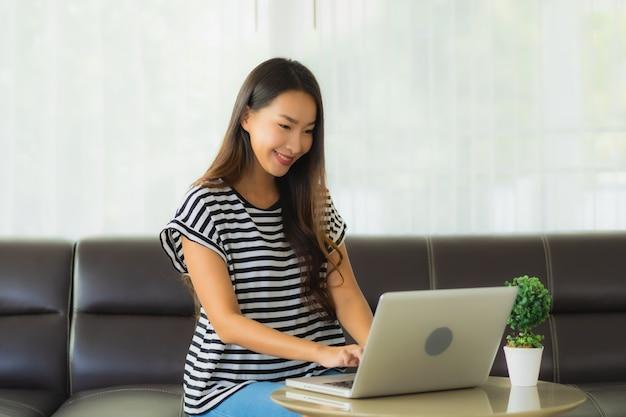 Portrait de la belle jeune femme asiatique à l'aide d'un ordinateur portable sur le canapé