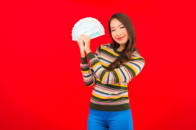 Portrait belle jeune femme asiatique avec de l'argent comptant et téléphone mobile sur mur rouge