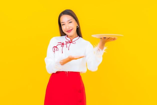 Portrait belle jeune femme asiatique avec assiette à vaisselle sur jaune