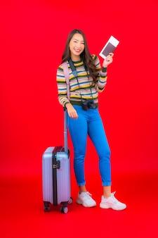 Portrait belle jeune femme asiatique avec bagages et carte d'embarquement sur mur rouge