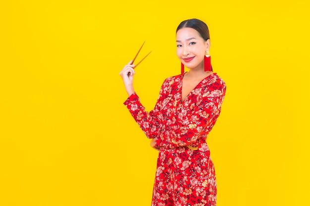 Portrait belle jeune femme asiatique avec des baguettes sur un mur isolé de couleur