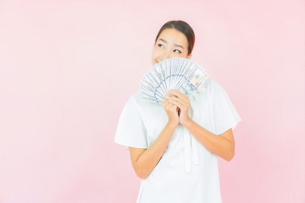 Portrait belle jeune femme asiatique avec beaucoup d'argent et d'argent sur le mur de couleur rose