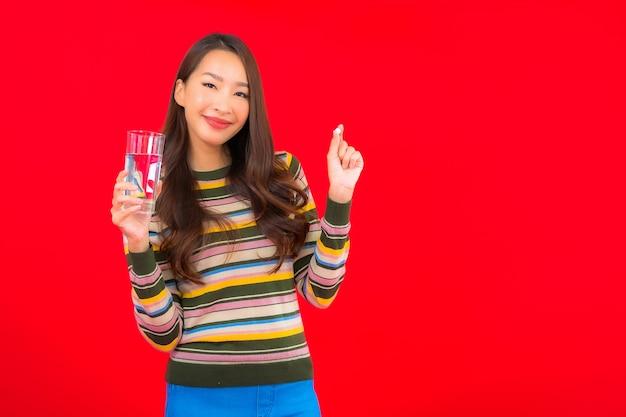 Portrait belle jeune femme asiatique avec boire de l'eau et des pilules sur le mur rouge