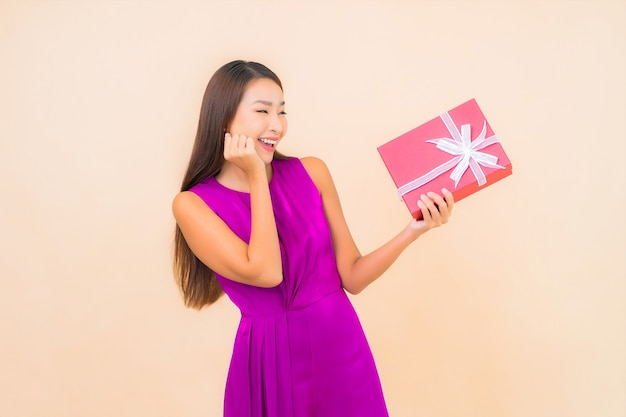 Portrait belle jeune femme asiatique avec boîte-cadeau rouge sur fond isolé de couleur