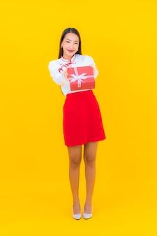 Portrait belle jeune femme asiatique avec boîte-cadeau rouge sur jaune
