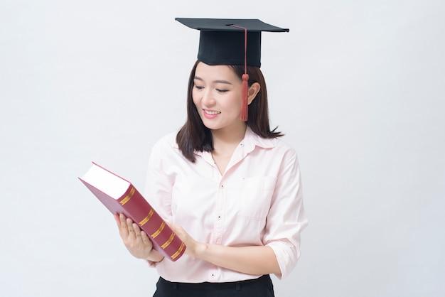 Un portrait de la belle jeune femme asiatique avec bonnet de l'éducation sur l'espace blanc studio, concept de l'éducation.