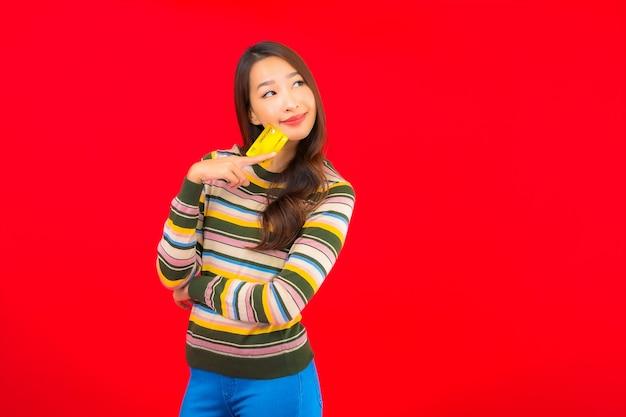 Portrait belle jeune femme asiatique avec carte de crédit sur mur isolé rouge