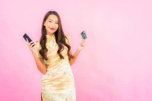 Portrait belle jeune femme asiatique avec carte de crédit et téléphone mobile sur le mur de couleur rose