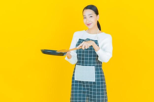Portrait belle jeune femme asiatique avec casserole et grosse cuillère sur jaune