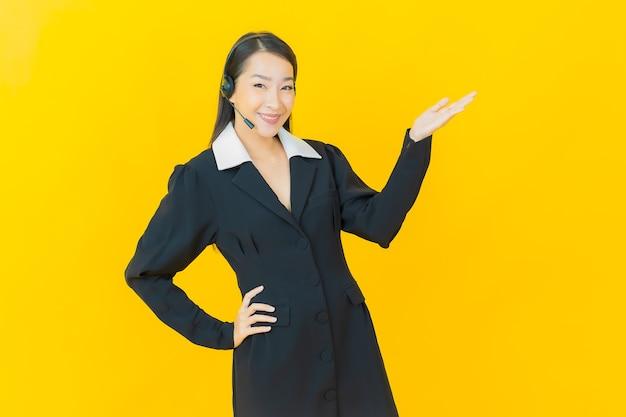 Portrait belle jeune femme asiatique avec centre d'appels centre de service client sur mur de couleur jaune