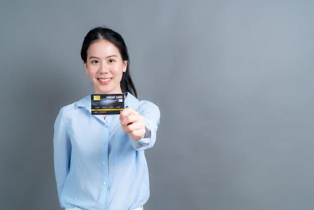 Portrait d'une belle jeune femme asiatique en chemise bleue montrant la carte de crédit avec copie espace sur mur gris