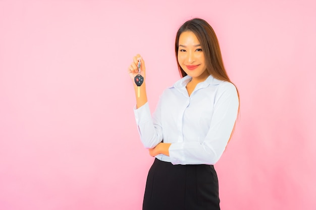Portrait belle jeune femme asiatique avec clé de voiture sur mur isolé rose