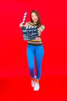Portrait belle jeune femme asiatique avec coupe ardoise de film sur mur isolé rouge