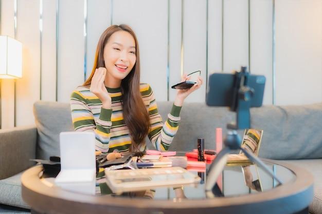Portrait de la belle jeune femme asiatique critiques et utilise des cosmétiques sur le canapé