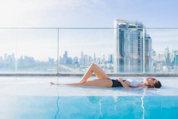 Portrait belle jeune femme asiatique détend les loisirs autour de la piscine