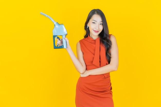 Portrait belle jeune femme asiatique feul pompe à essence sur jaune