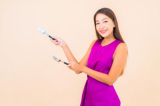 Portrait belle jeune femme asiatique avec fourchette et cuillère prêt à manger sur fond de couleur