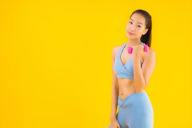 Portrait belle jeune femme asiatique avec haltère et vêtements de sport sur jaune