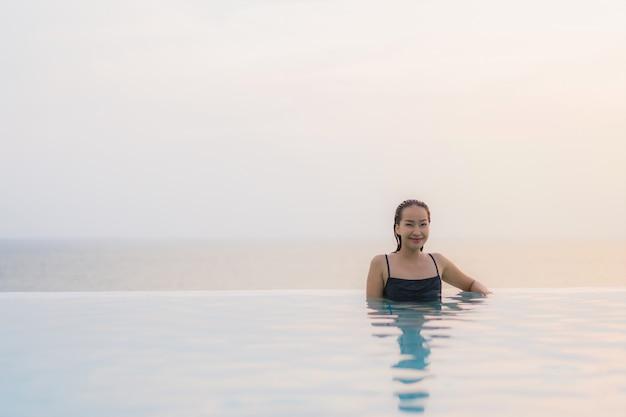 Portrait belle jeune femme asiatique heureux sourire se détendre autour de la piscine dans l'hôtel resort