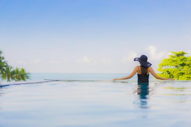 Portrait belle jeune femme asiatique heureux sourire se détendre piscine extérieure dans un hôtel