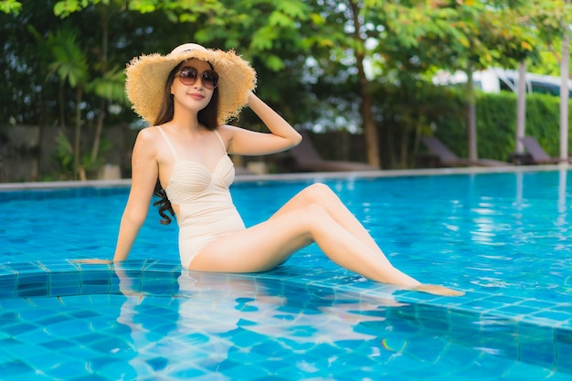 Portrait belle jeune femme asiatique heureux sourire se détendre piscine en plein air dans la station
