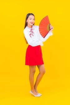 Portrait belle jeune femme asiatique avec une lettre d'enveloppes rouges sur jaune