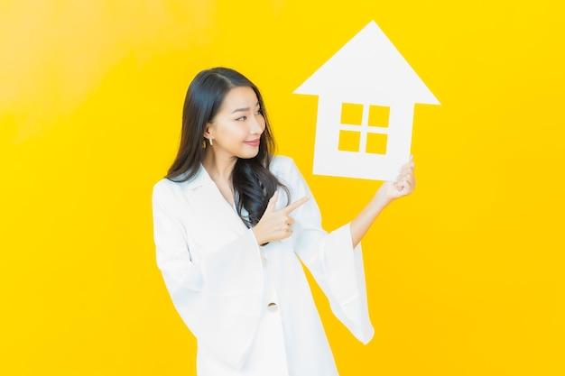 Portrait d'une belle jeune femme asiatique avec une maison en papier sur un mur jaune