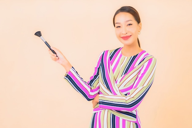 Portrait belle jeune femme asiatique avec maquillage pinceau cosmétique sur la couleur