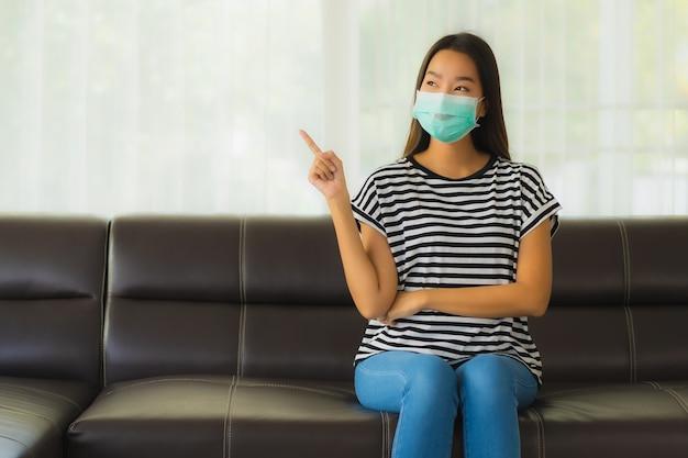 Portrait de la belle jeune femme asiatique avec masque sur canapé
