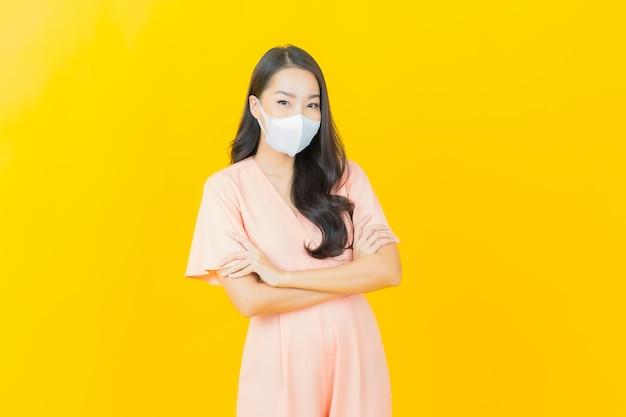 Portrait belle jeune femme asiatique avec masque pour protéger le virus covid19 sur un mur de couleur jaune